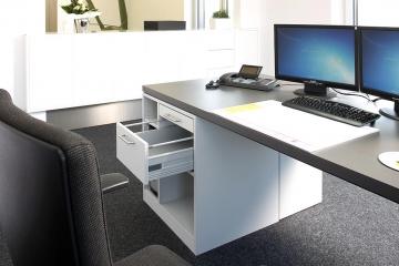 Schreibtisch aus Holz mit Schubladen-Element.