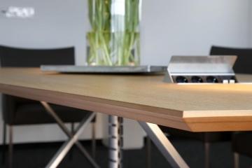 Konferenztisch mit integrierten Steckdosen und Kabeln für Beamer, Telefon, etc.