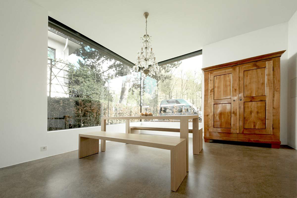 Ein Moderner Holztisch Mit Passenden Bänken In Reizvollem Kontrast Zu Einem  Alten Schrank.