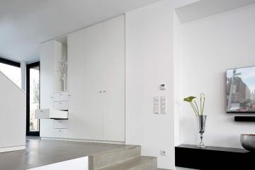 Moderne Garderobe in weiß. Hinter der Tür hängen die Jacken und Mäntel.